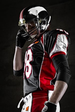 Portrait of american football player looking aside on dark background
