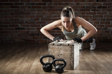 Young fit woman pushing up on brick background