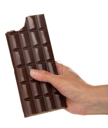 Photo pour Main féminine avec un carreau de chocolat noir, où la tranche est mordue, isolé sur blanc - image libre de droit