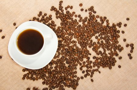 White cup of hot coffee, grains on a sacking