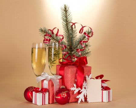 Champagne, fir-tree branch with tinsel, gift boxes, toys and blank card on a beige background