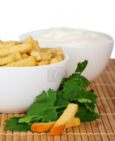 Croutons, sour cream and the parsley a close up isolated on white