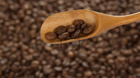 Wooden spoon with coffee, against coffee grains