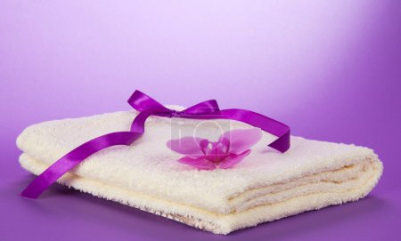 The fluffy, terry towel decorated with a flower of an orchid and a ribbon on a violet background