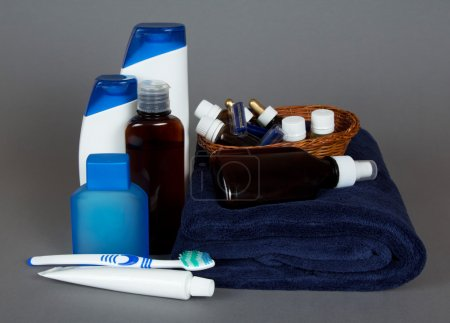 Toilet accessories, towel, toothbrush and toothpaste, on a gray background