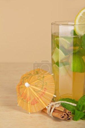 Cinnamon sticks, a lemon slice, an umbrella, closeup, on a table