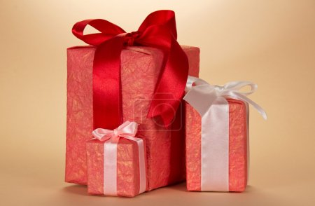 Three gift boxes with a ribbon and bow, on a beige background