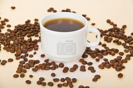 Cup with coffee, coffee grains, a napkin, on a beige background
