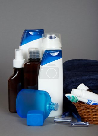 Many different color tubes and bottles for hygiene, health and beauty on a grey background