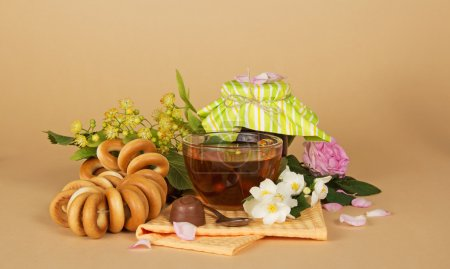 Cup of tea, heap of bagels, chocolate, and flowers