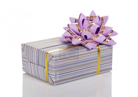 The gift box decorated with a golden tape and a bow