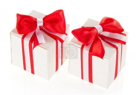Two white gift boxes with a red bow and the tape, isolated on white