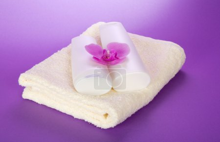 Towel and set for the bathing, decorated with an orchid flower on the violet