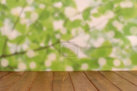 Photo for Empty wooden deck table with foliage bokeh background. Ready for product display montage. - Royalty Free Image