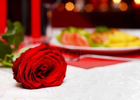 Photo pour Rose sur une table devant de délicieux plats lors d'un dîner romantique - image libre de droit