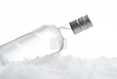 Bottle of vodka lying on ice on white background