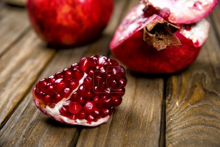 Ripe juicy pomegranate on wooden table