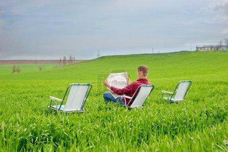 Man reading a newspaper outdoors