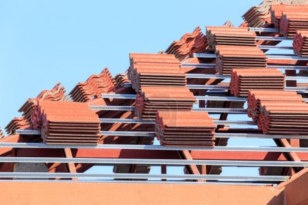 roof under construction with stacks of roof tiles for home build