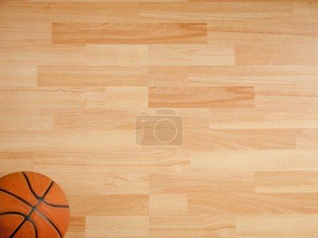 Photo pour Un ballon officiel orange sur un terrain de basket feuillu - image libre de droit
