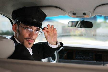 Photo pour Portrait d'un beau chauffeur assis dans une voiture saluant un spectateur - image libre de droit