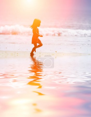 Photo for Child running on water at ocean beach at sunset. - Royalty Free Image