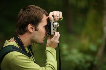Photo pour Photographe prise de vue avec appareil photo compact en forêt. DOF peu profond . - image libre de droit