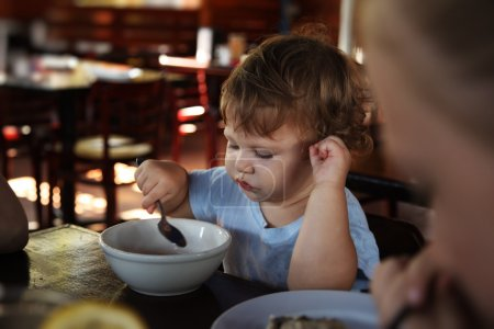 Cute 15 months old baby girl eating in restaurant....