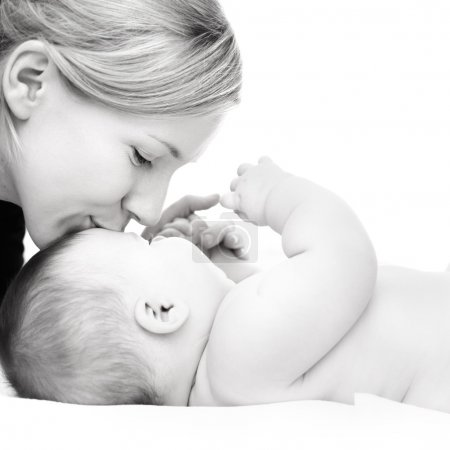 Photo for Happy mother kissing baby girl against white background - Royalty Free Image
