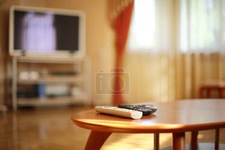 Photo pour Romouvoir contrôles sur table en bois, tv en arrière-plan. peu profond dof, mettant l'accent sur la distance de blanc. - image libre de droit