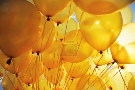 Photo for Background of bright yellow inflatable balloons up in the air, backlit by sun. - Royalty Free Image