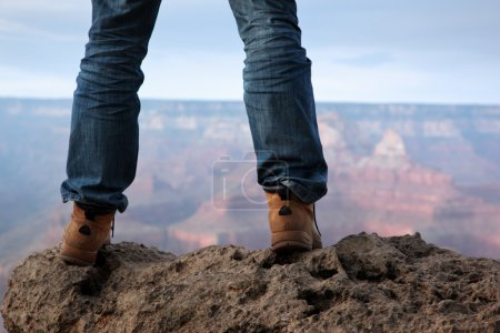 Photo for Man in hiking boots standing on edge of a cliff in Grand Canyon, Arizona. - Royalty Free Image