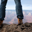 Man in hiking boots standing on edge of a cliff in...