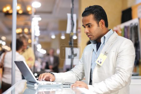 Photo for Young indian businessman using laptop computer at trade show. - Royalty Free Image