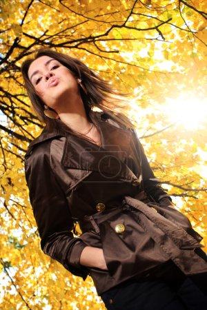 Photo pour Belle jeune femme sous les branches d'arbres au feuillage jaune d'automne dans le parc, soufflant un baiser . - image libre de droit