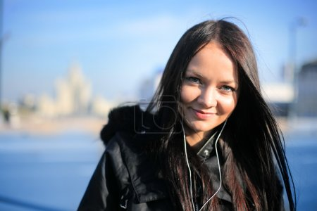Photo pour Belle fille souriant et écoutant de la musique portable à l'extérieur dans la ville d'hiver. DOF peu profond, se concentrer sur les yeux . - image libre de droit