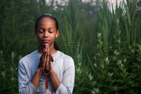 Photo for Teenage girl praying outdoors at twilight. Shallow DOF. - Royalty Free Image