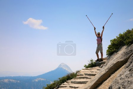 Woman standing on top of a mountain