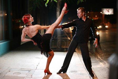Photo pour Couple dansant dans une rue dans la nuit. - image libre de droit