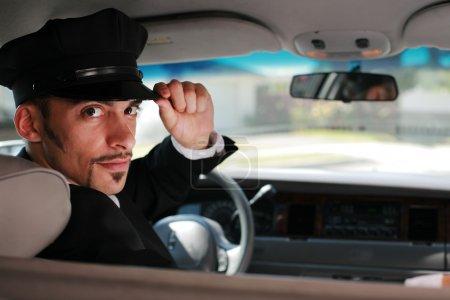 Photo pour Portrait d'un beau chauffeur assis dans une voiture saluant un spectateur . - image libre de droit
