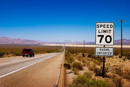 Photo pour Route du désert à l'horizon avec un panneau de limitation de vitesse sur un côté . - image libre de droit