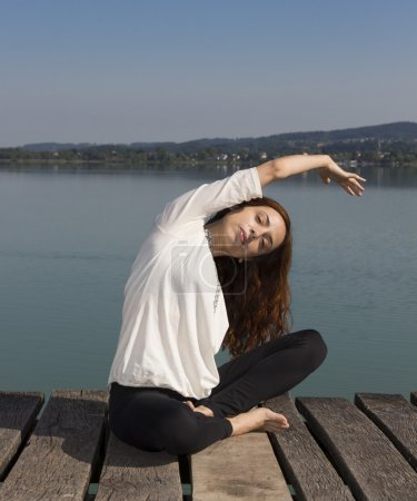 Woman doing seated side bend during yoga outdoors