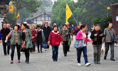 Photo pour LANGZHONG ANCIENT CITY (SICHUAN), CHINE : Une guide avec drapeau jaune conduit son groupe de visiteurs chinois à une visite guidée de la ville historique - image libre de droit