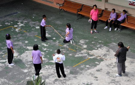 Photo for Bangkok, Thailand: School children playing jump rope in the schoolyard at Wat Hua Lamphong - Royalty Free Image