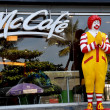 Pattaya, Thailand: A larger-than-life sized Ronald McDonald with hands clasped in the traditional Thai wei greeting stands in front of a McDonald's fast food restaurant