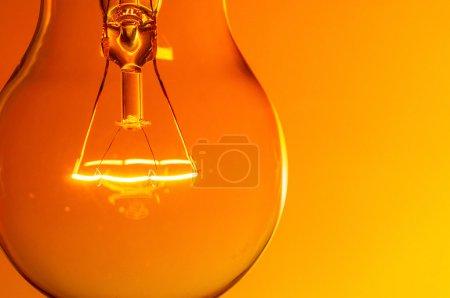 Photo for Close up glowing light bulb on orange background - Royalty Free Image