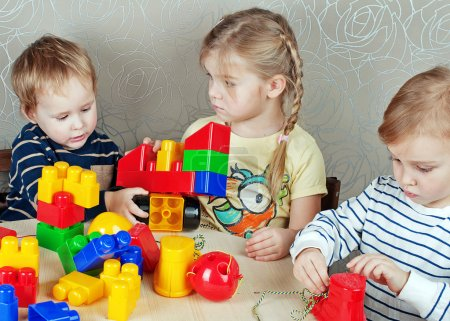 three children playing with toys