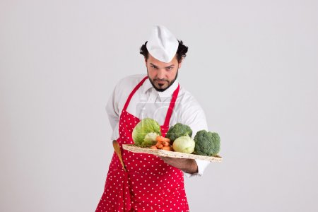 Photo for Italian Chief cook is Holding Wicker Tray Full of Vegetables Isolated on White Background - Royalty Free Image