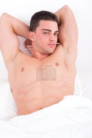 attractive muscular man lying in bed