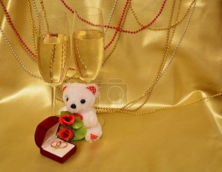 Photo pour Anneaux de mariage, verrerie avec vin mousseux, ours en peluche sur fond doré. Une composition Saint-Valentin : draperie satinée, décorée de perles, qui est boîte rouge velours avec des alliances et il ya deux verres de vin mousseux - image libre de droit